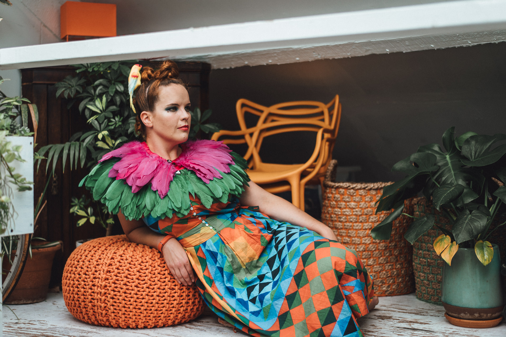 Colourfully dressed woman with parrot in her hair. Quirky london branding shoot