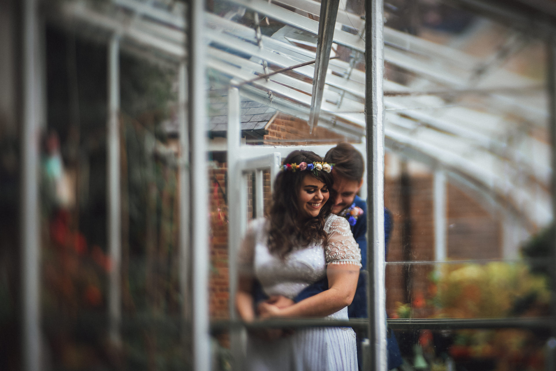 Couple embrace in a green house. Romantic, creative St Albans wedding photography