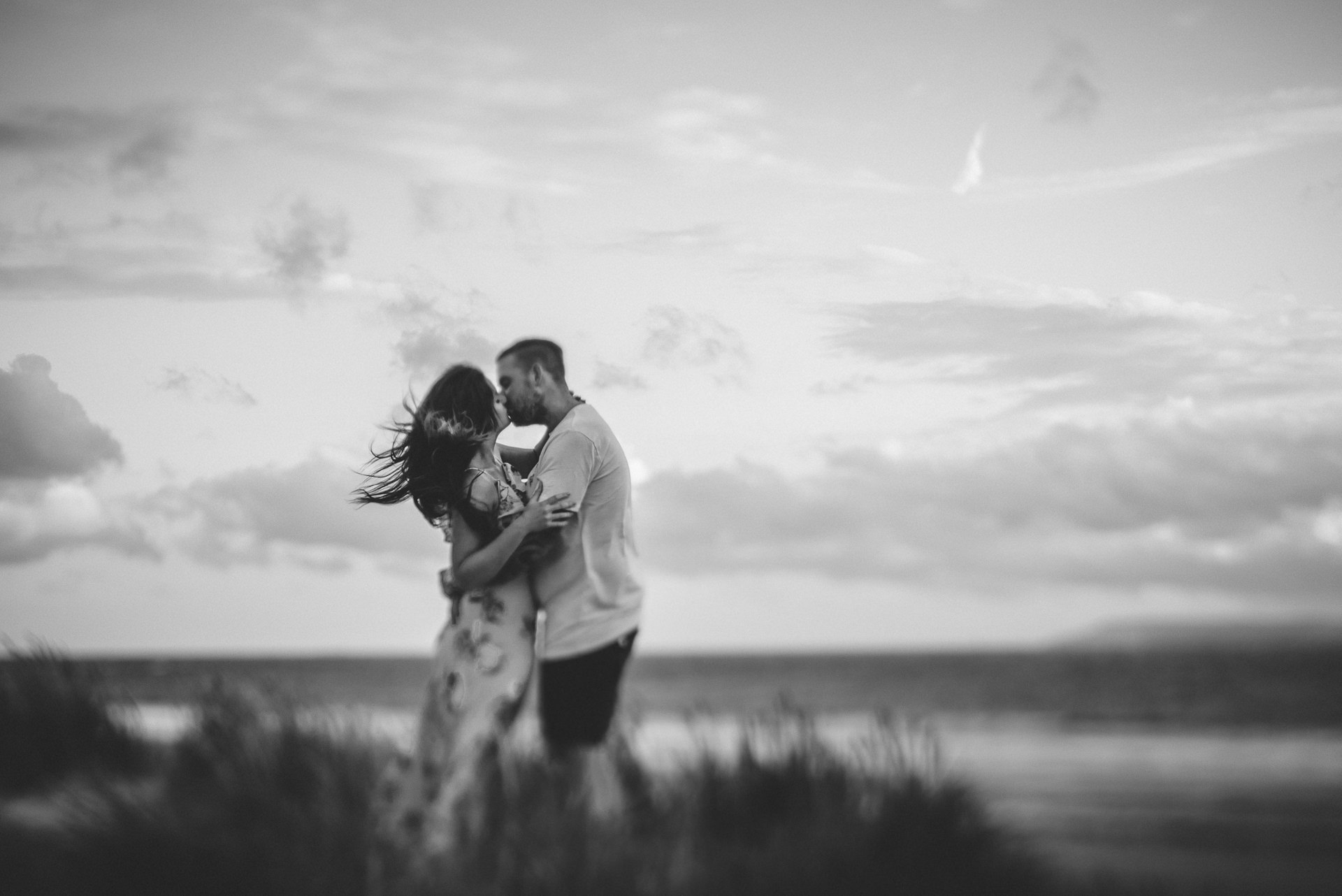 Couple kissing on a beach. Romantic Engagement photography ideas