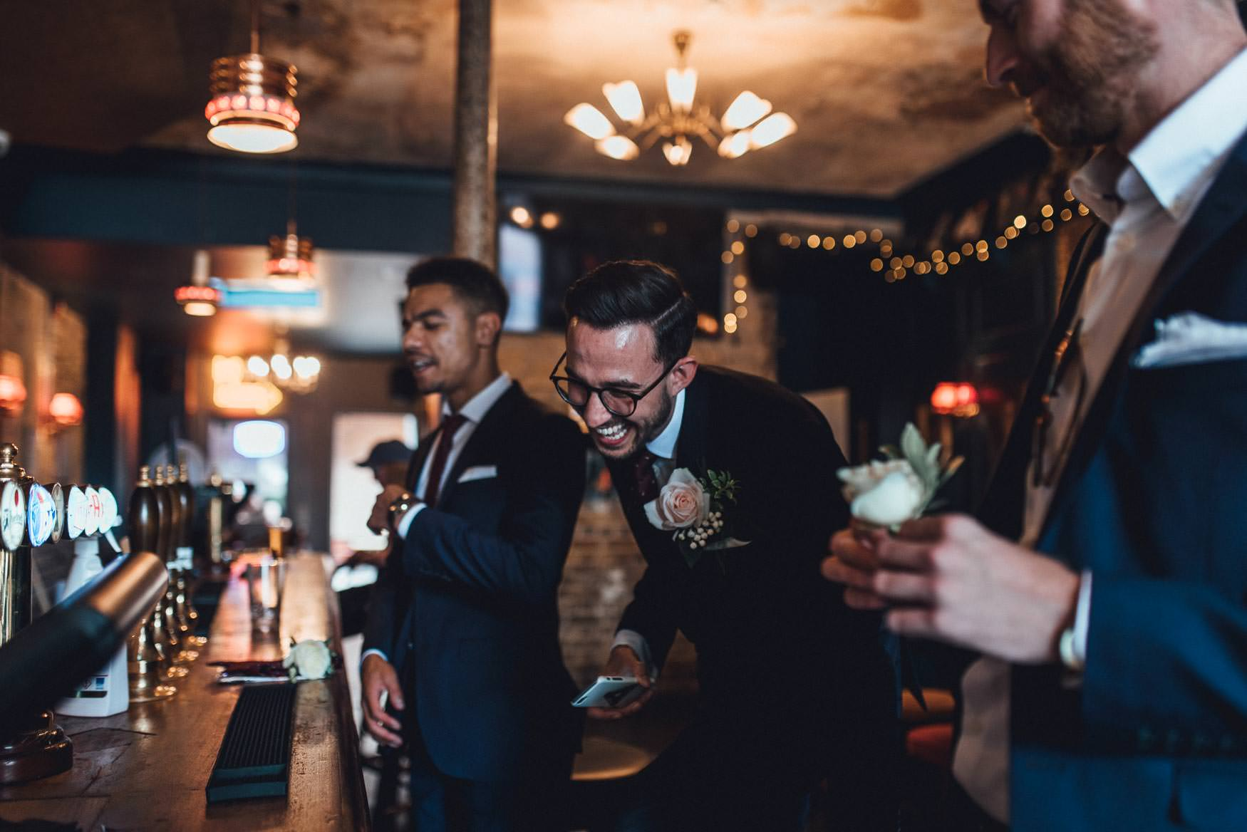 Groom laughing with his grooms men. Cool, fun London Wedding Photography