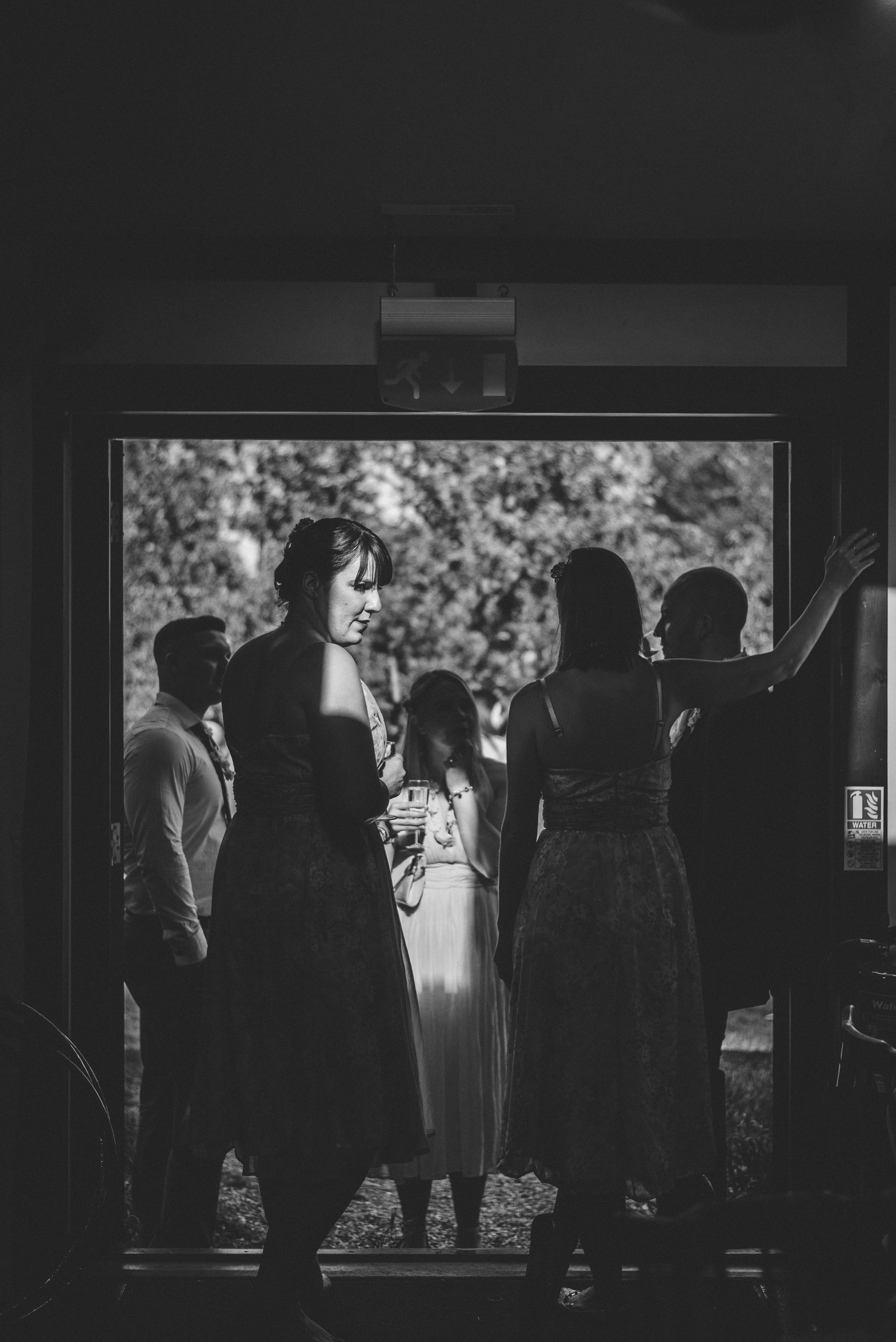 Woman standing in a small patch of light. Creative, documentary London wedding photography
