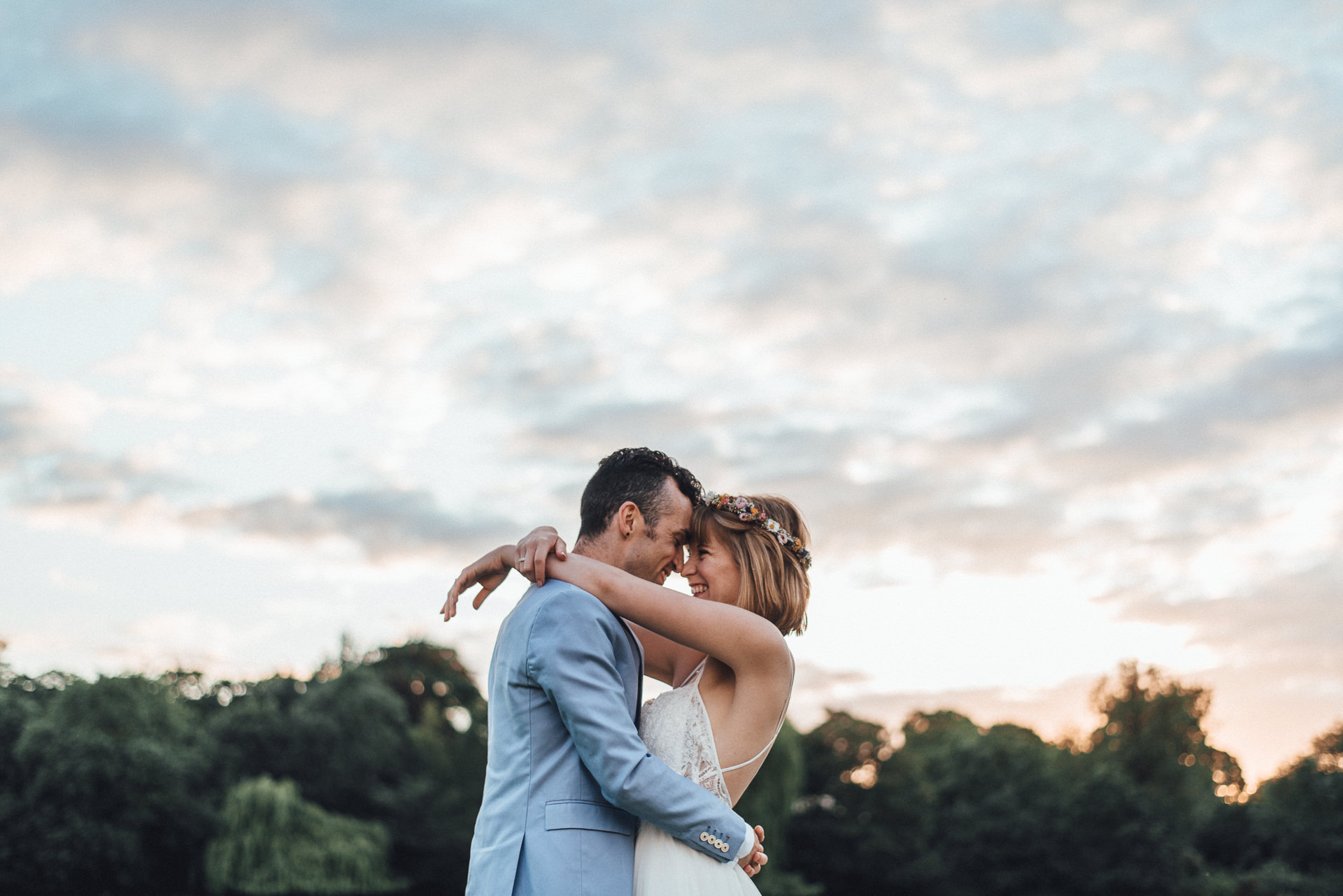 Couple embrace under a dramatic sky. Romantic Cambridge wedding photography