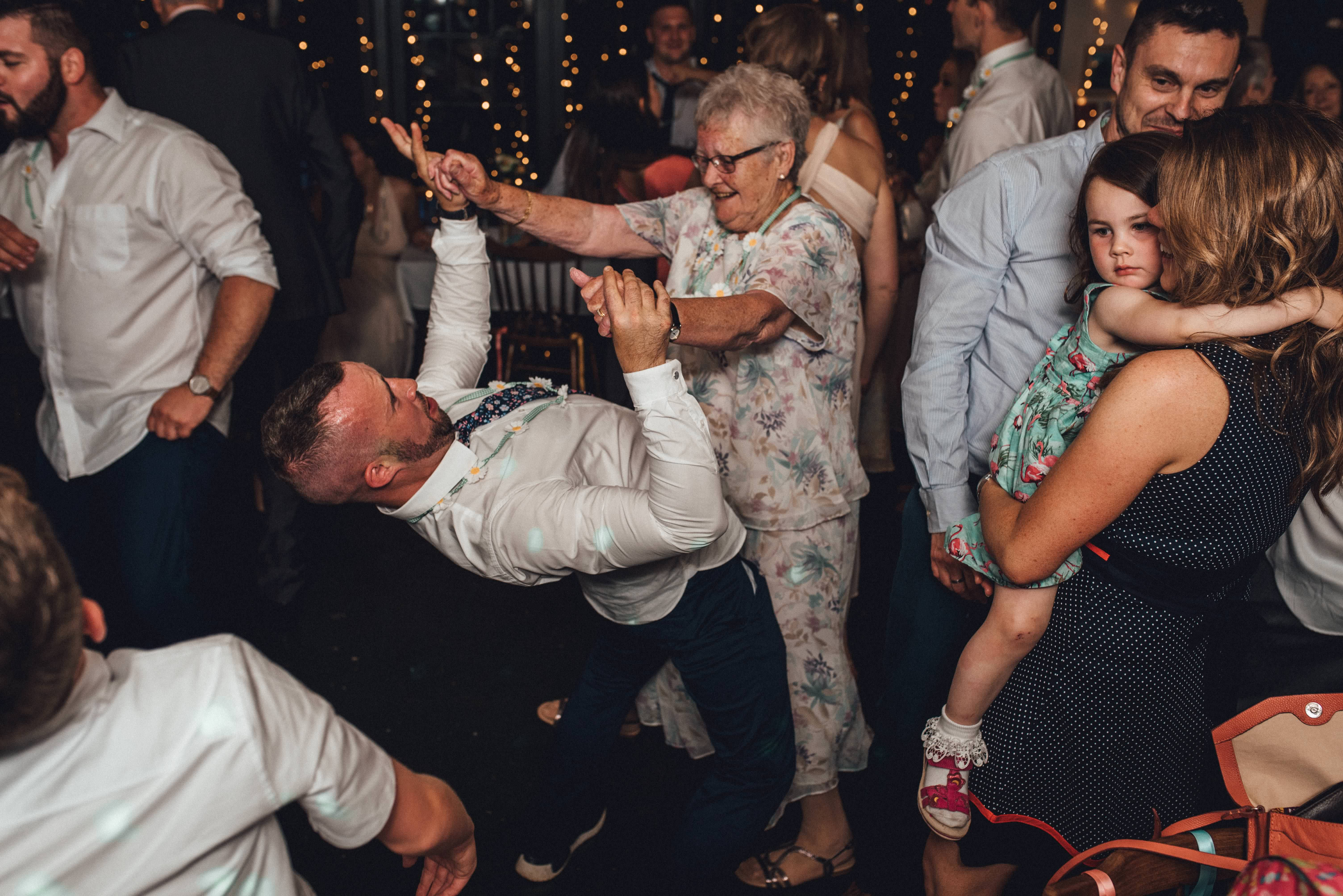 Man dancing energetically with his grandma! Fun, documentary wedding photography