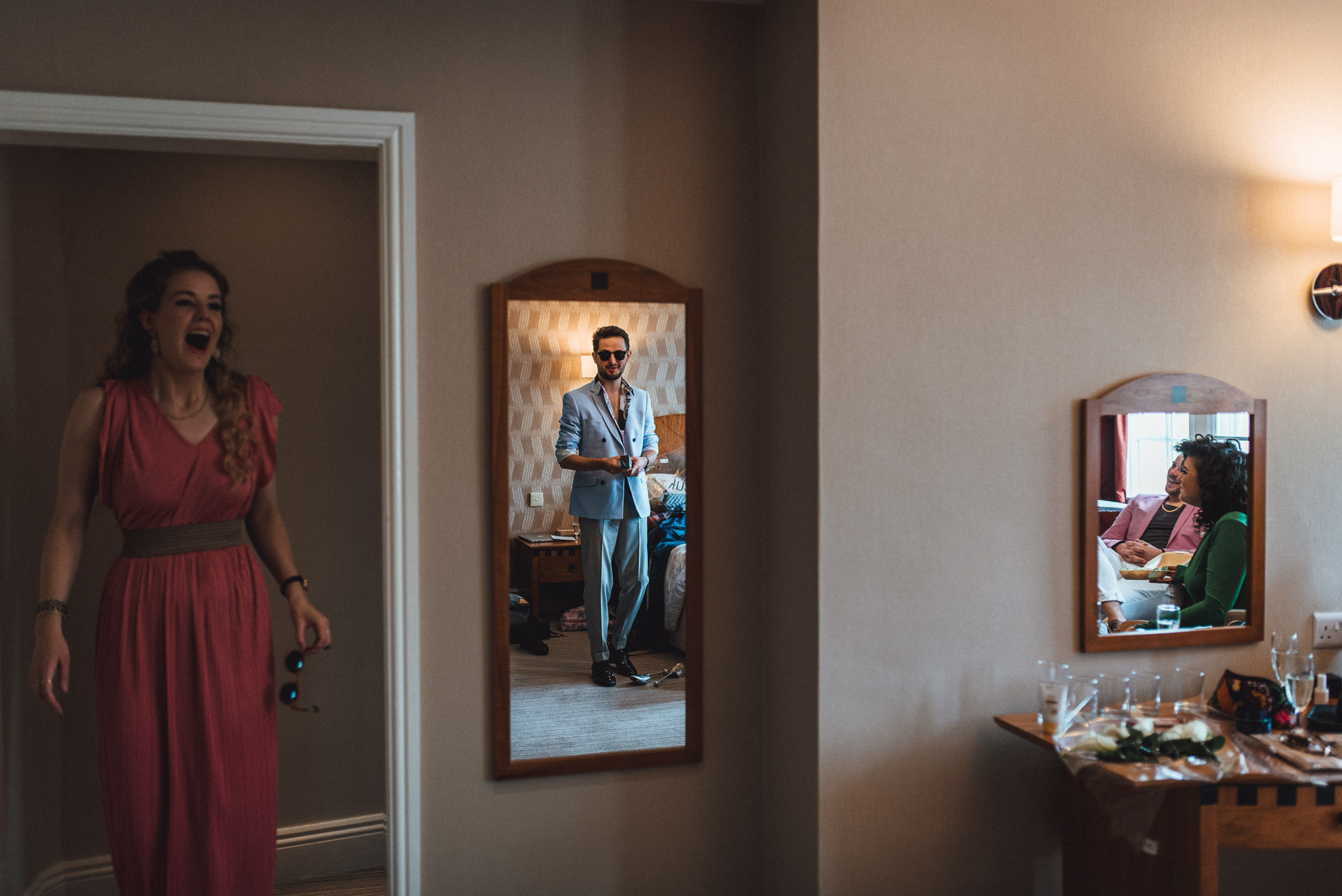 Groom getting ready, reflections of him and his friends in the mirror. Fun, creative wedding photography ideas.