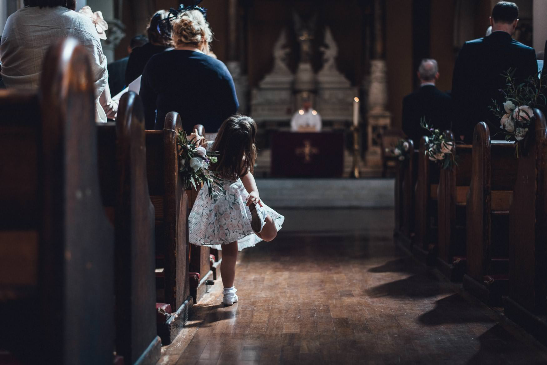 Child playing in the middle of the isle in a church. Creative, alternative London wedding photography