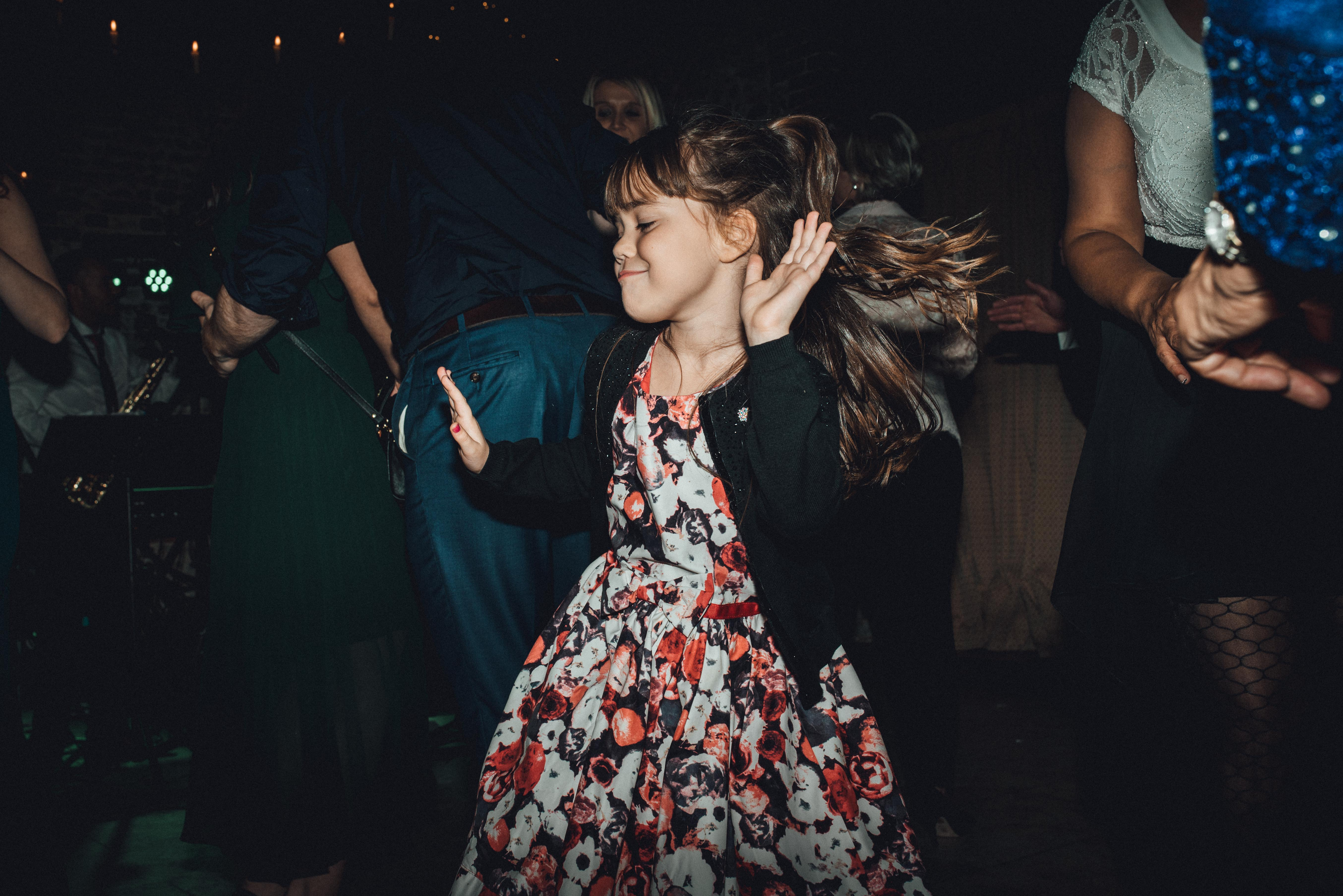 Young girl on the dance floor. Fun documentary wedding photography
