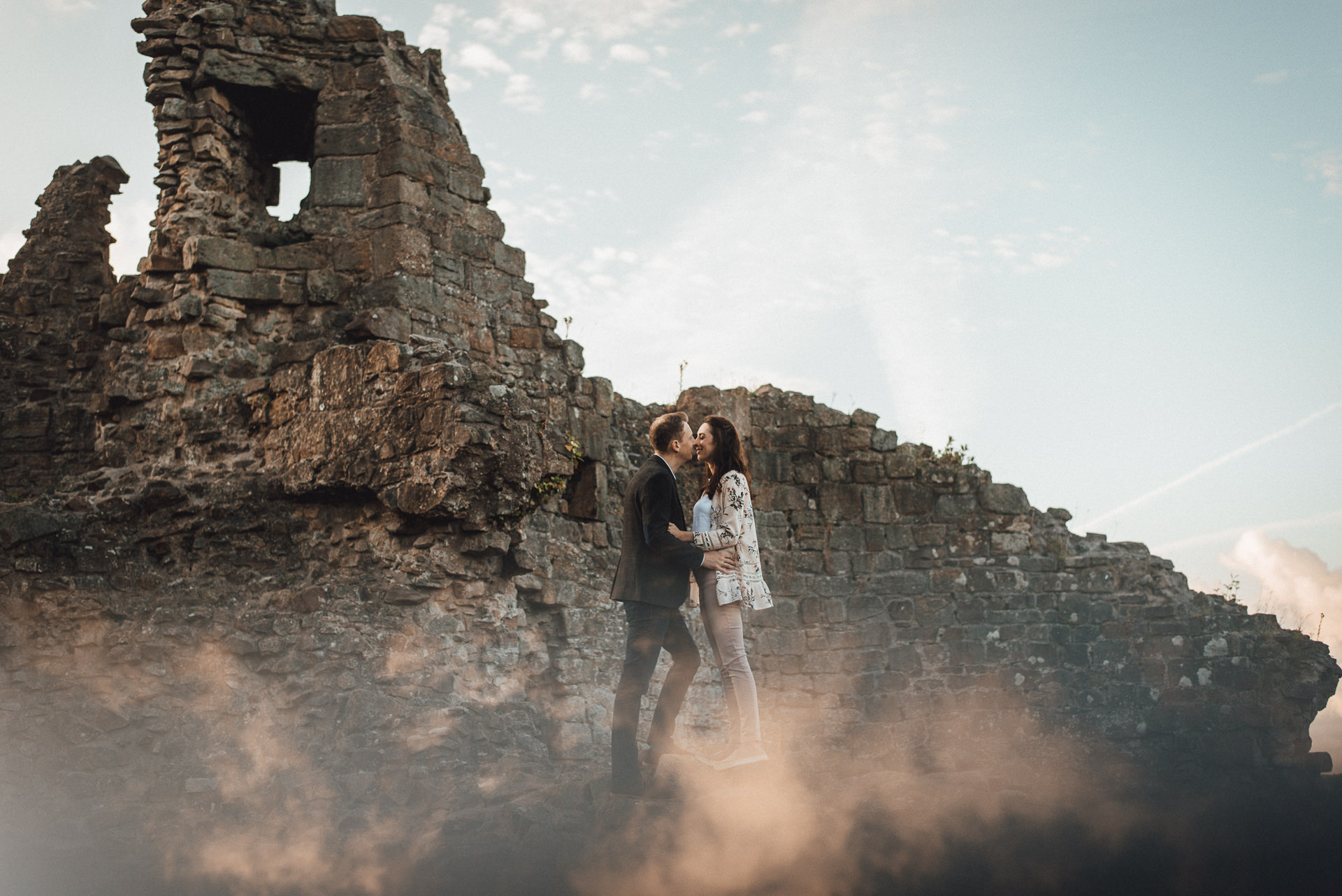 Couple kiss in the middle of castle ruins. Romantic engagement photography ideas.