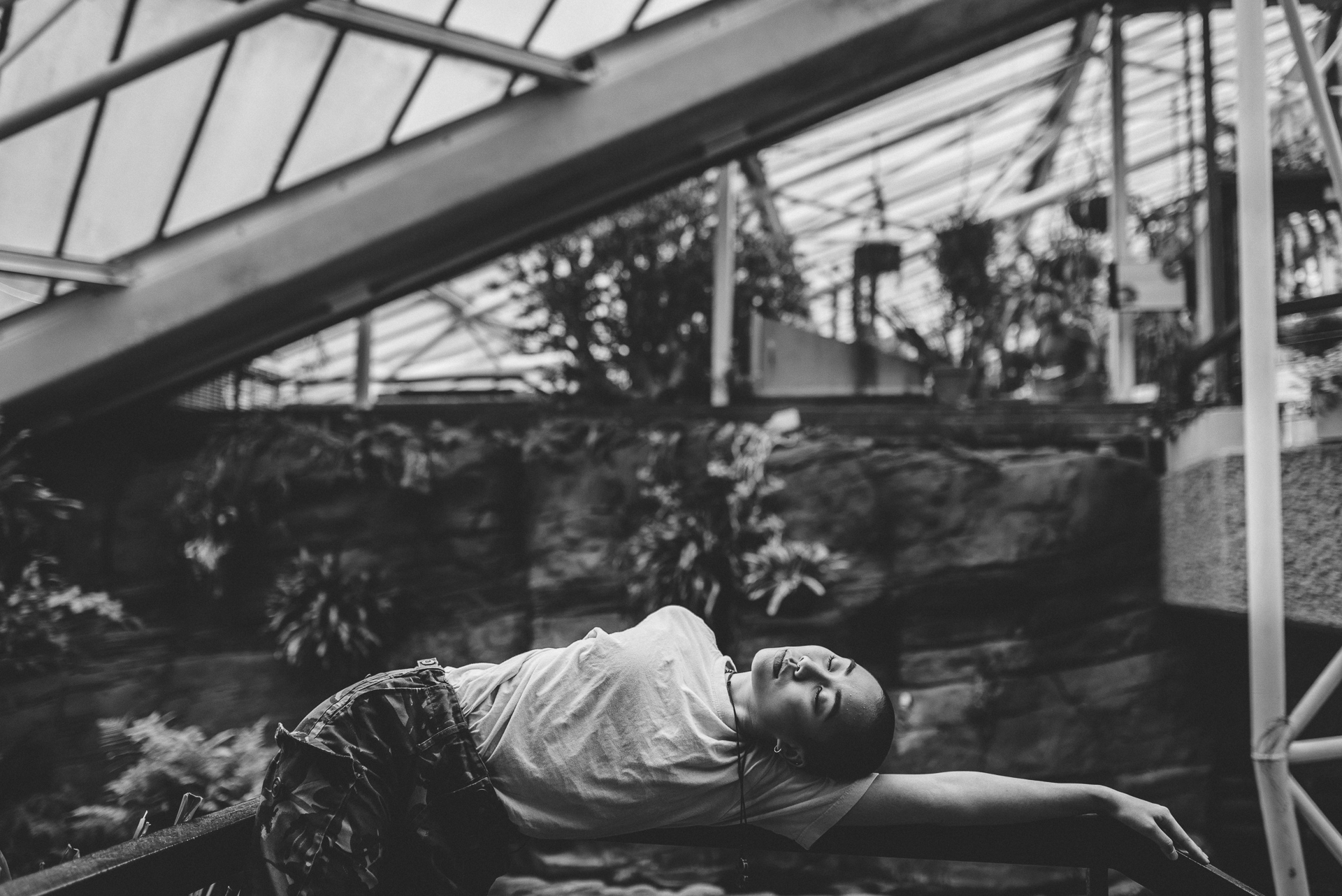 Dancer lying on banister in the Barbican Conservatory. London dance photography
