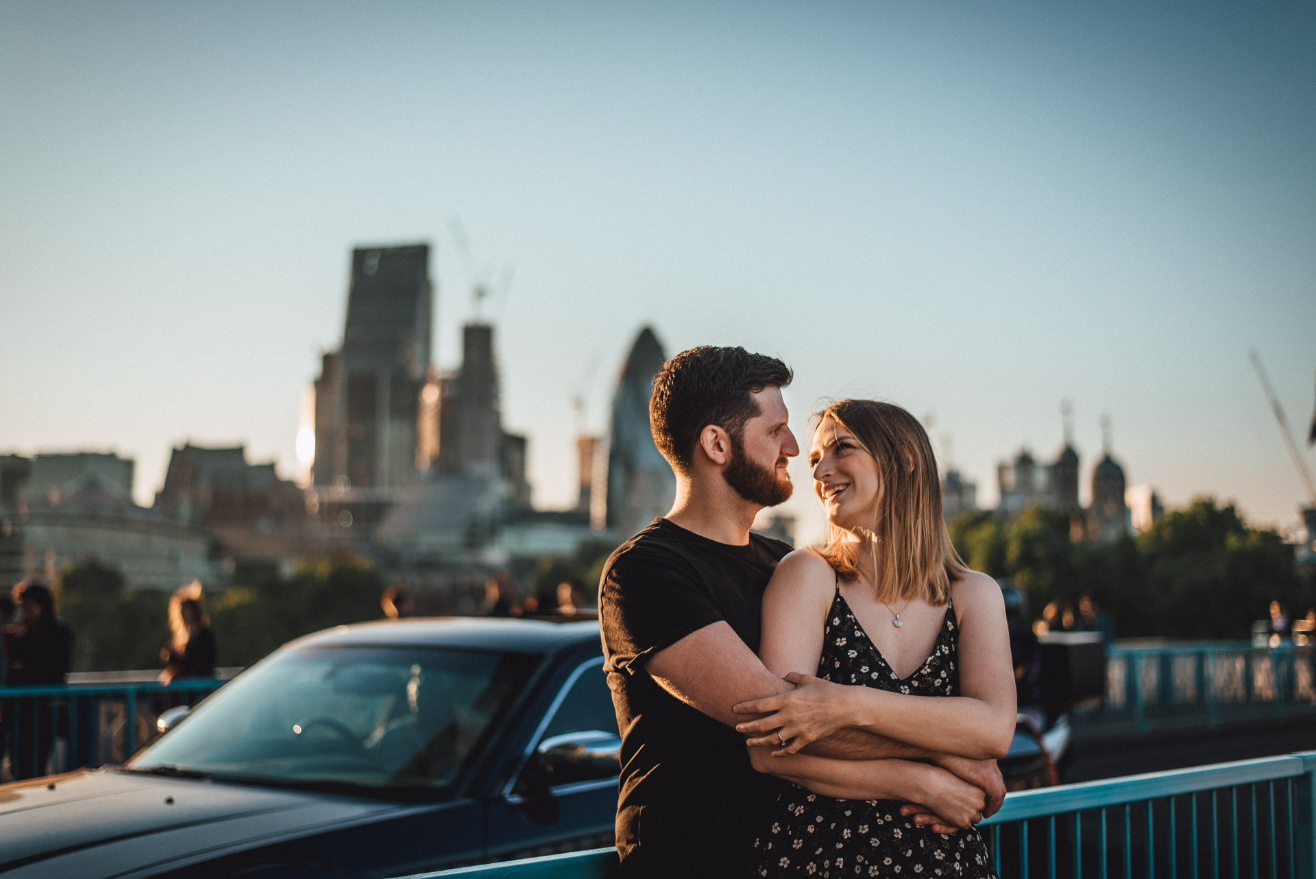 Couple embrace on Tower Bridge, London. Fun, romantic london engagement shoot ideas