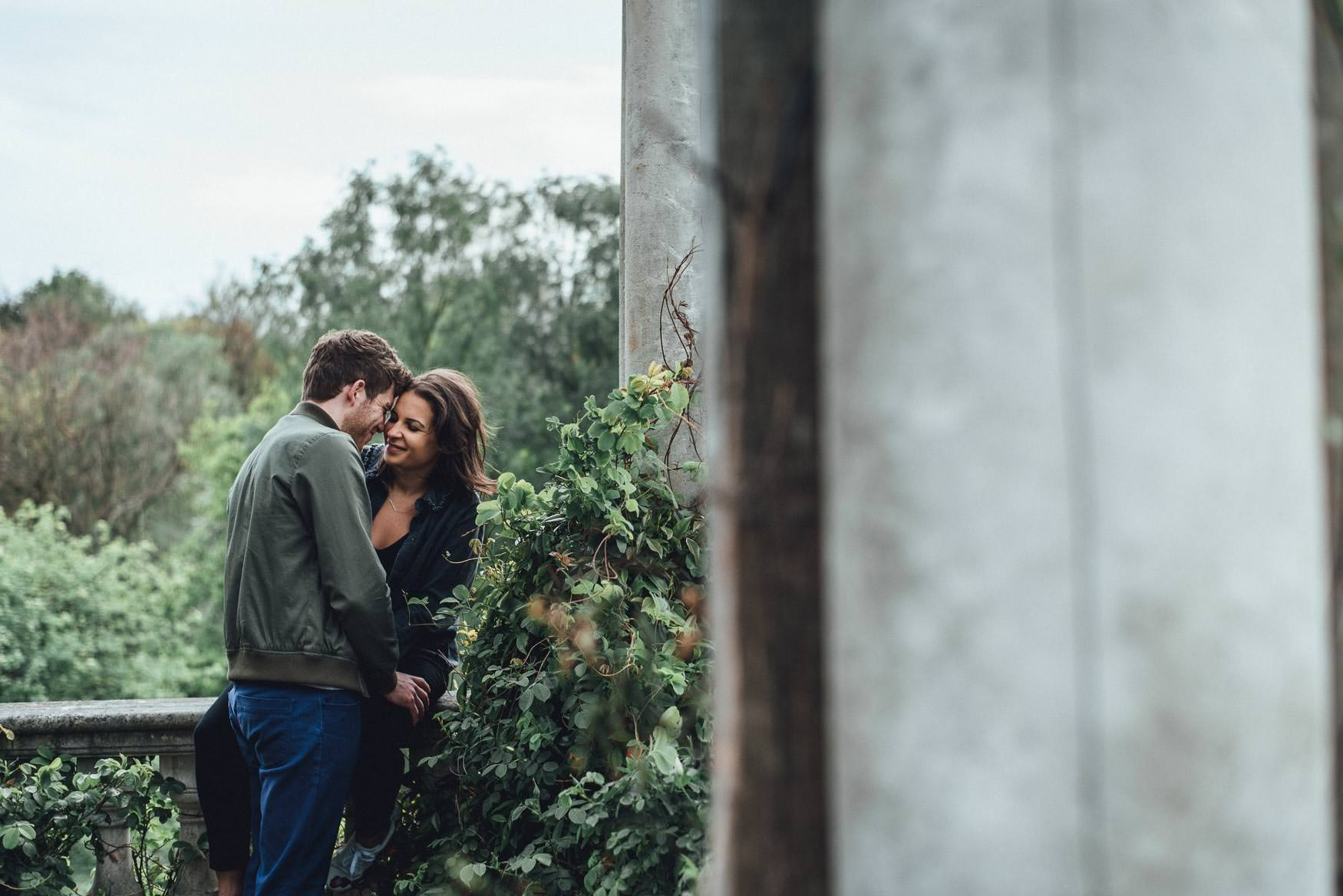 Couple smiling and embracing, surrounded by foliage. Romantic, fun london engagement shoot.