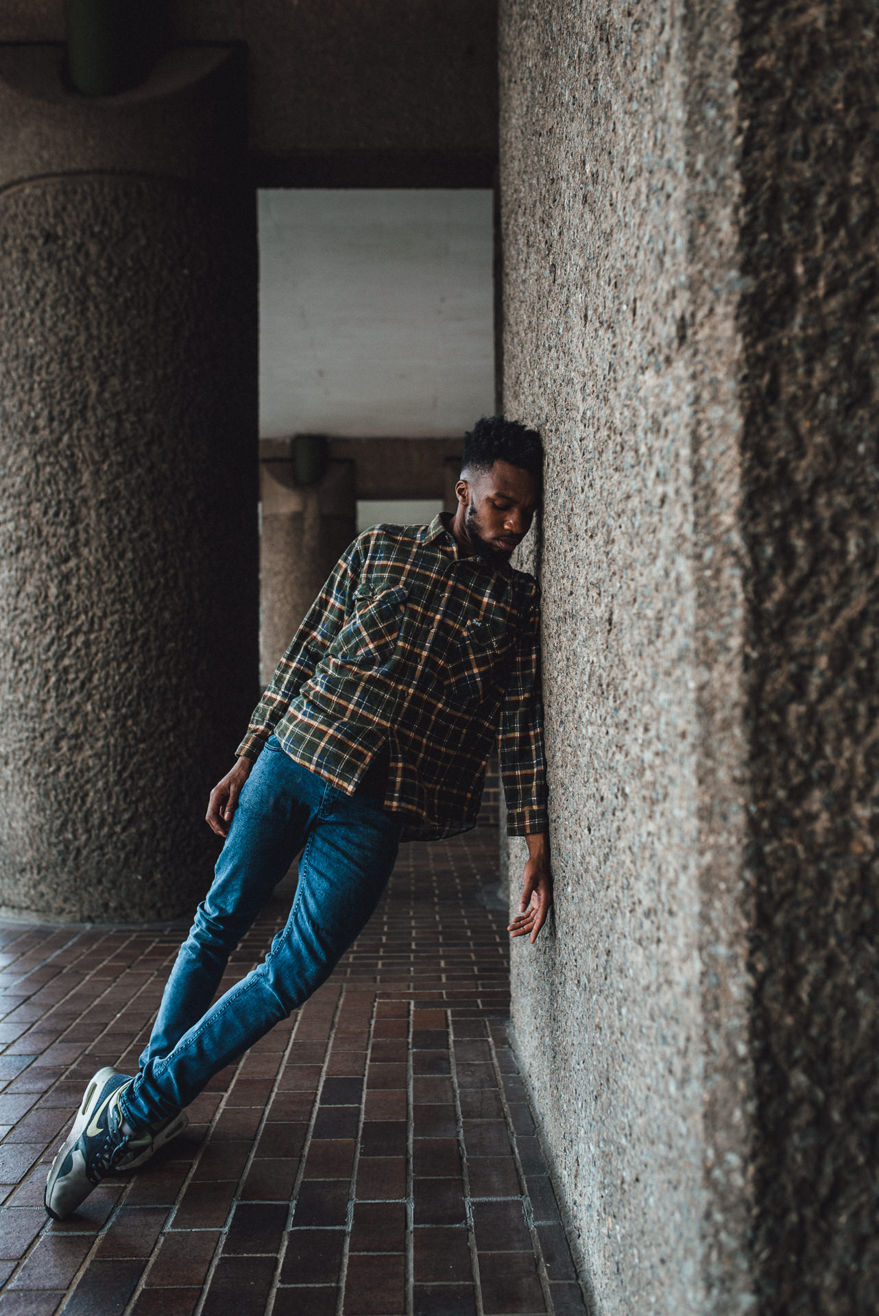 Male Dancer leans against a wall in the Barbican Centre, London