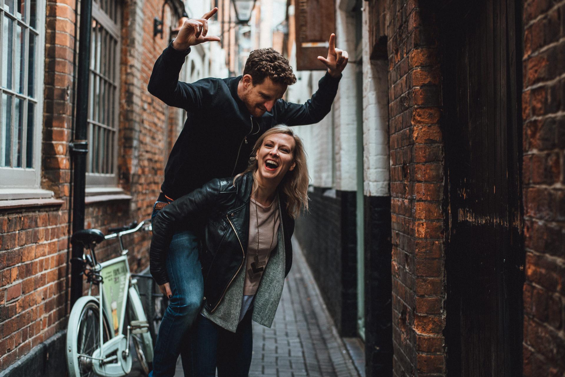 Woman gives man a piggy back. Fun Oxford Engagement shoot