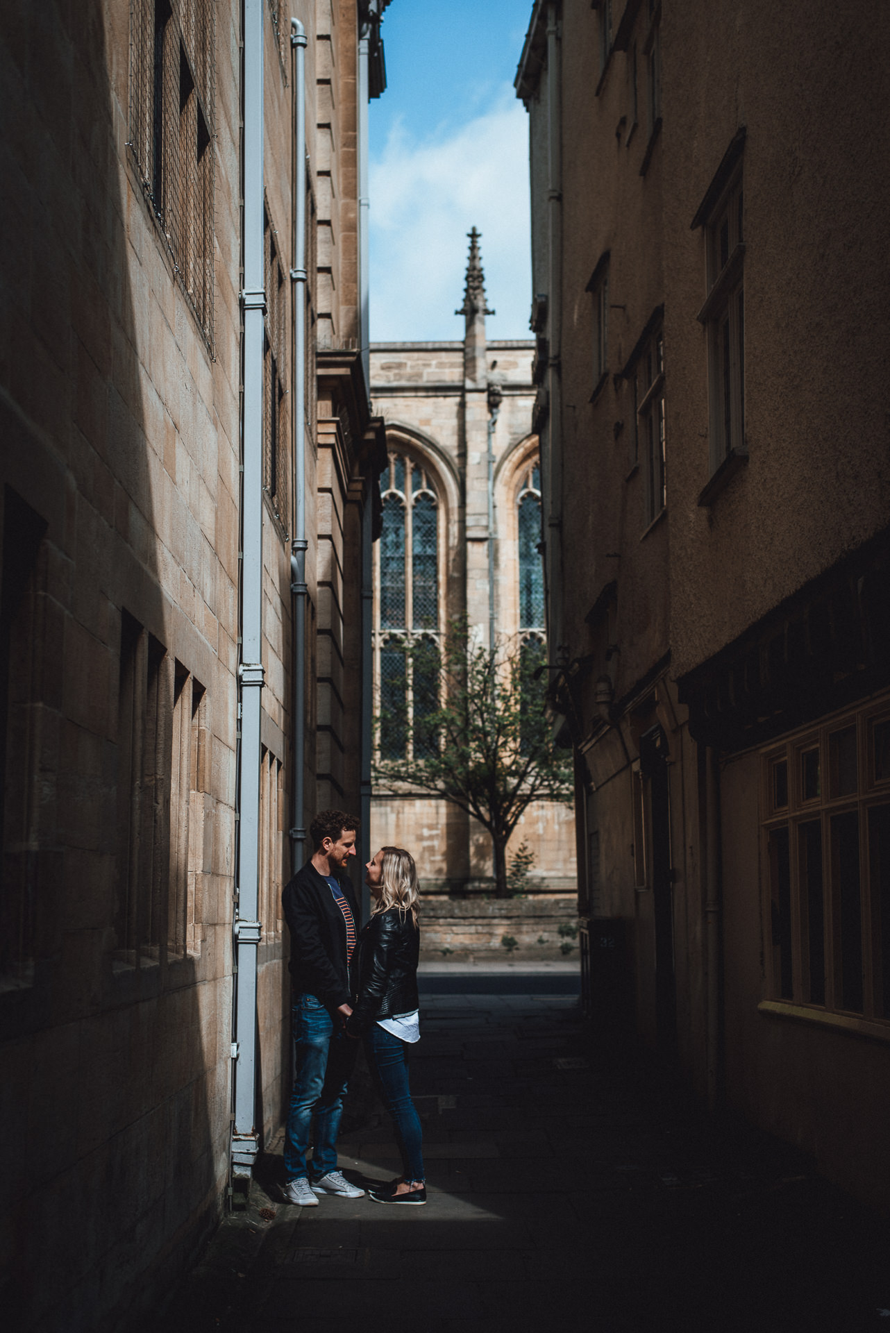 Couple hold hands in a small patch of light. Creative London Engagement shoot ideas