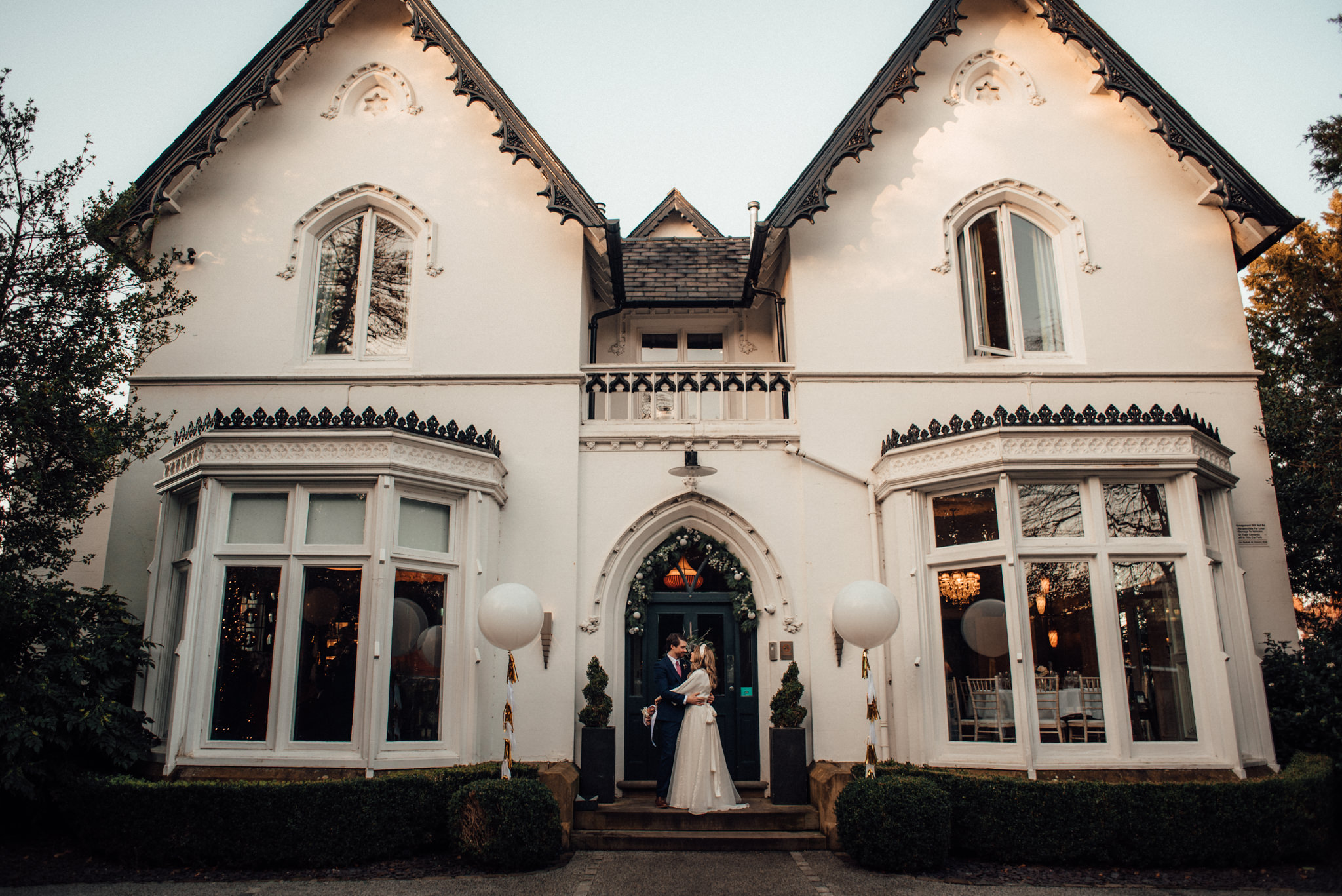 Newly wed couple cuddle in the doorway of Didsbury House Hotel