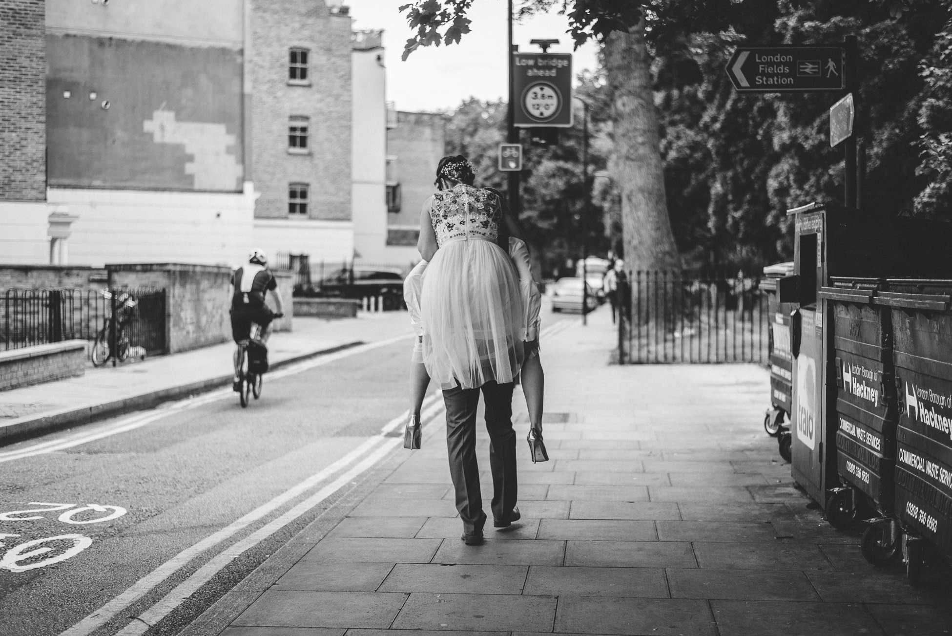 Groom gives bride a piggy back ride as they walk through London Fields Park - Urban Wedding Photography