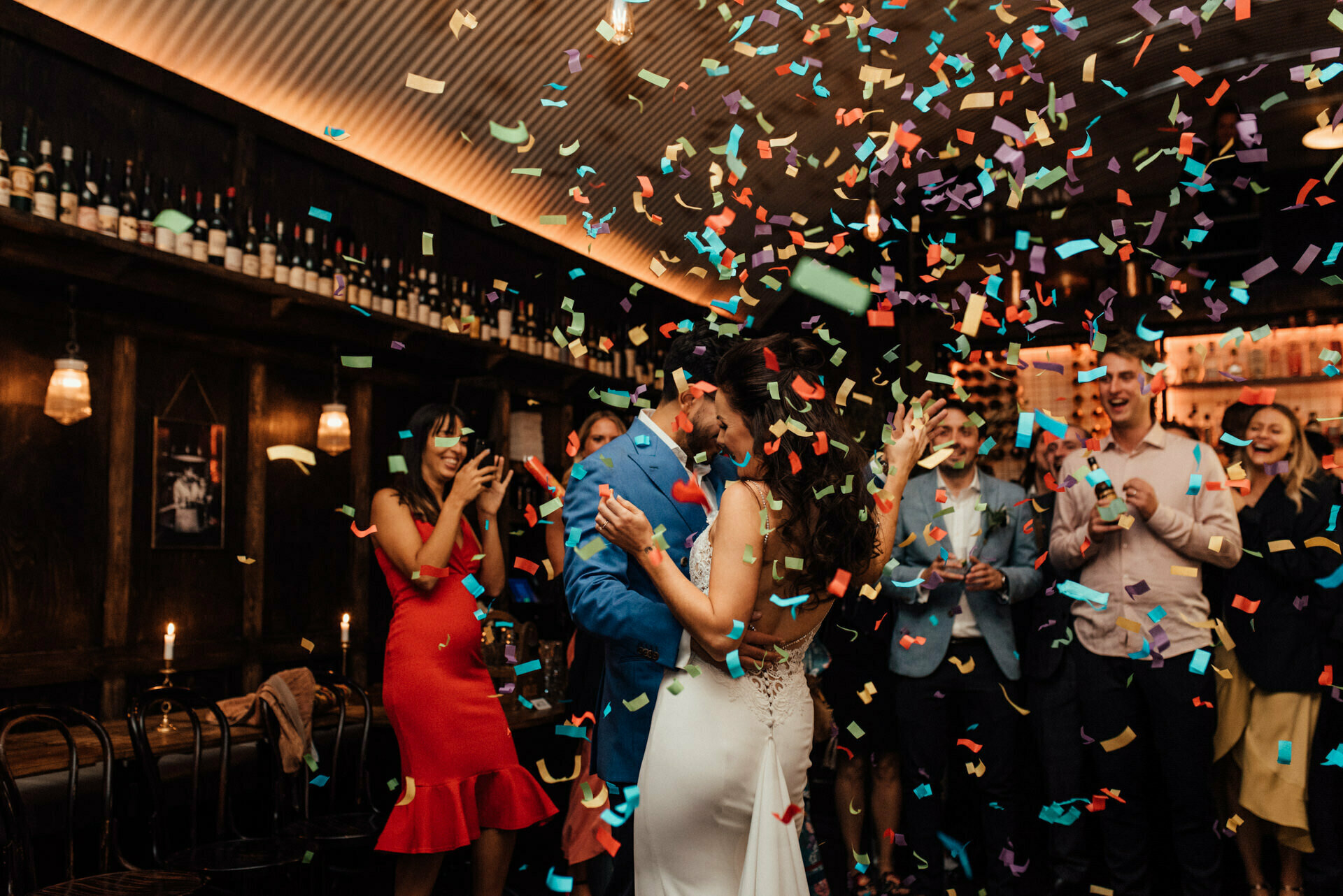 Bride and groom enjoy their first dance in a London wine bar, covered in colourful confetti
