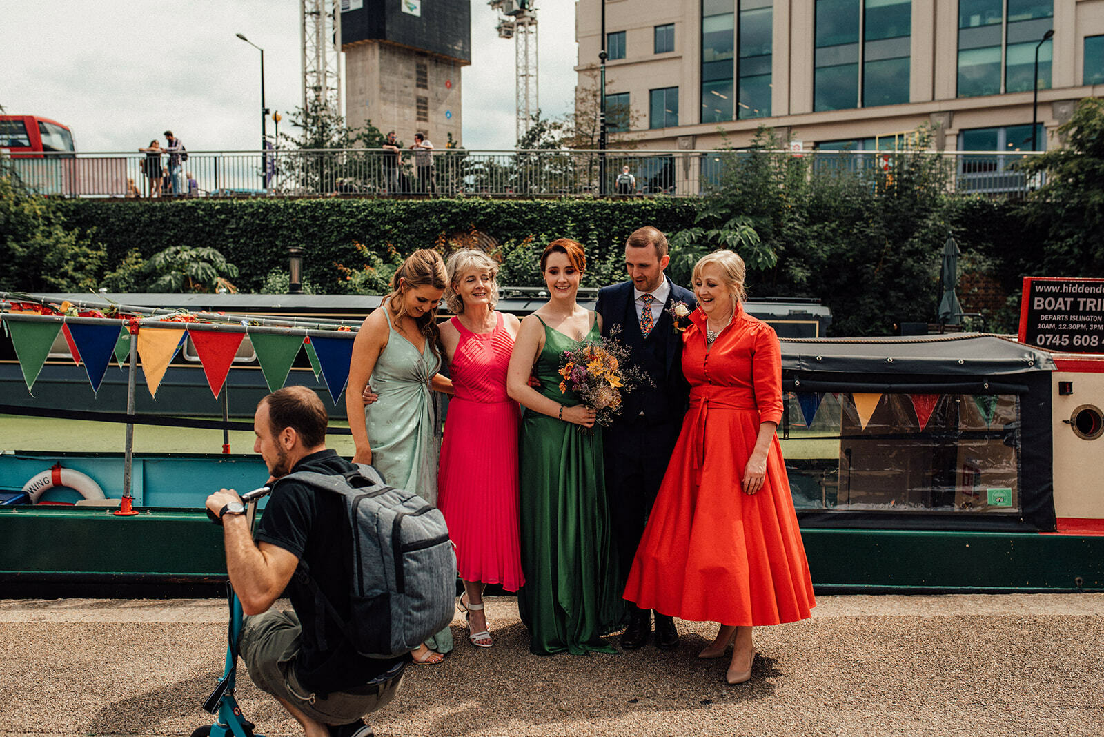 Wedding party gets photobombed by a man on a scooter as they pose for a portrait in front of canal boat in Kings Cross