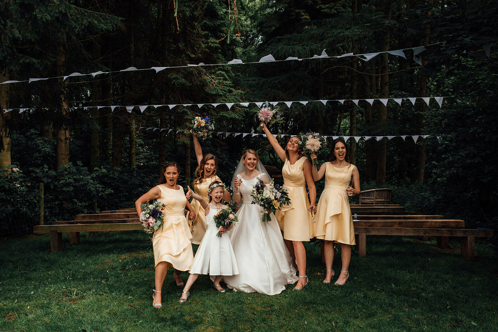 Bride and her bridesmaids do a silly pose in the woodland wedding ceremony area of Lineham Farm