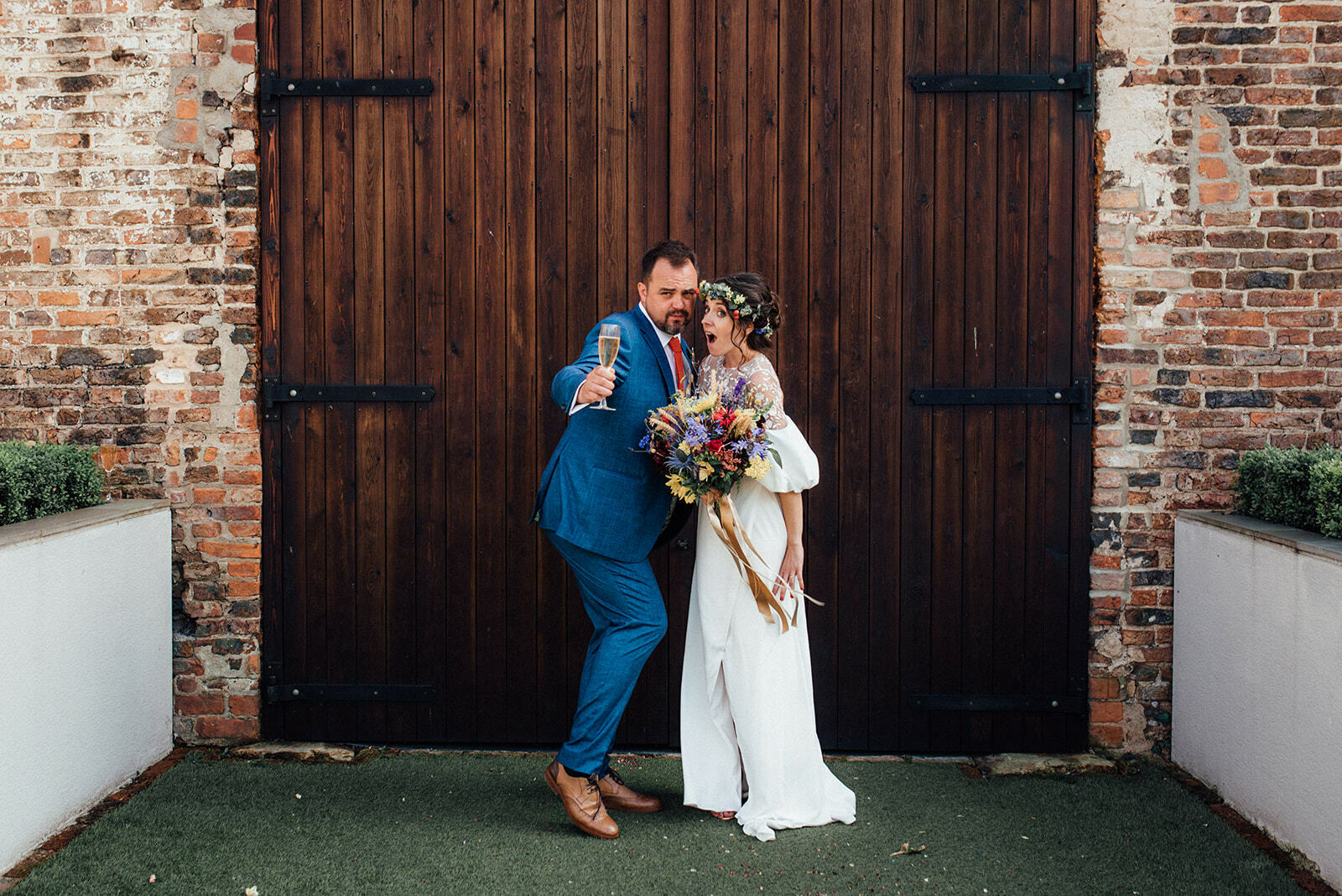 Bride and groom pose in front of the ban doors at The Normans
