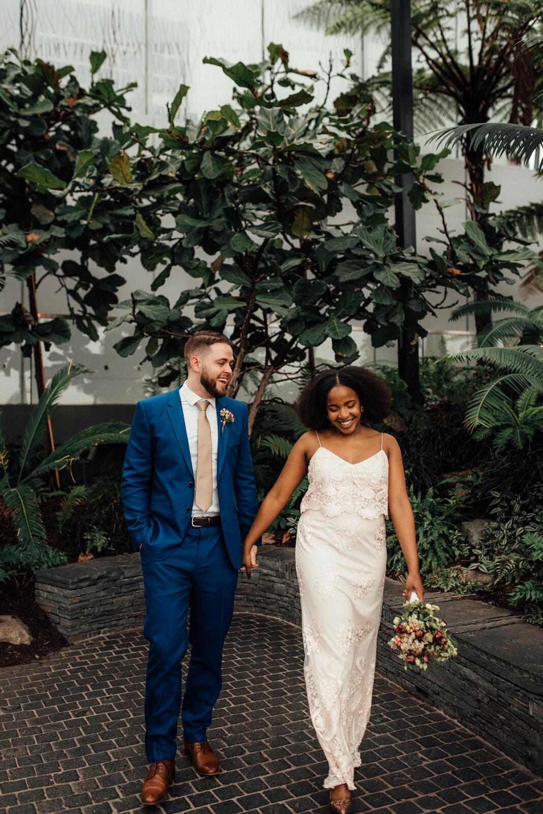 Newlywed couple walk hand in hand through London Sky Garden