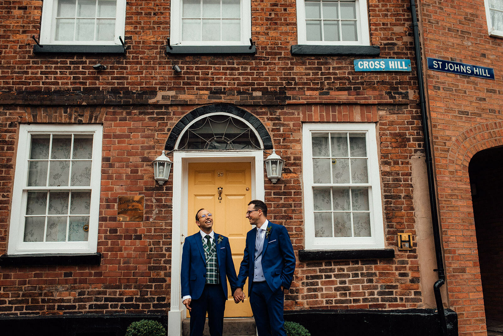 Newlywed grooms hold hands and smile in front of a yellow door in Shrewsbury