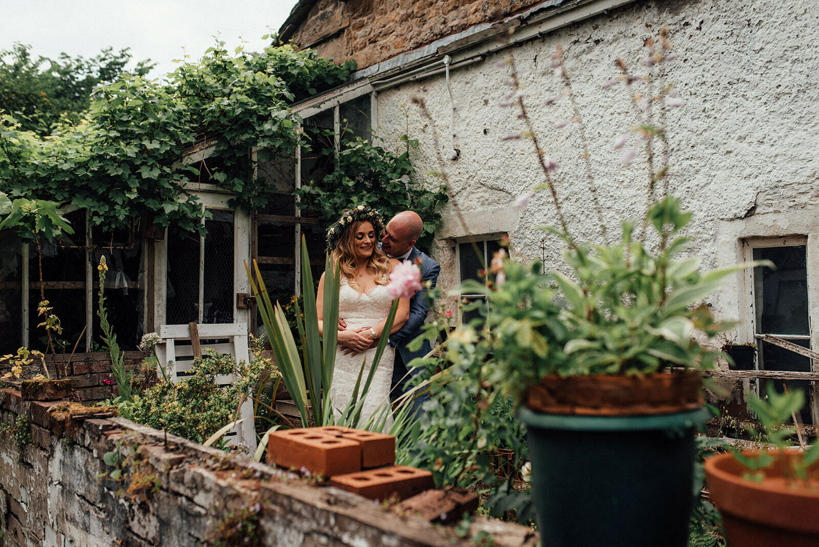 Bride and groom cuddle, surrounded by potted plants at their Pendle Heritage Centre Wedding