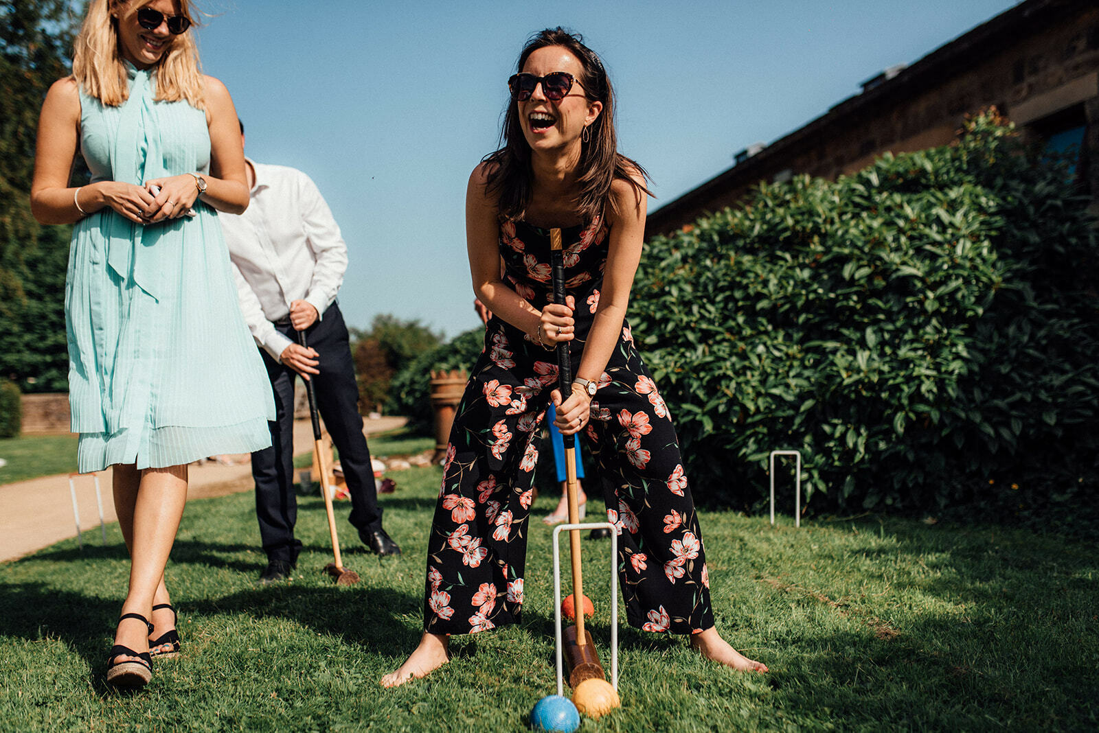 Guest laughs as she plays croquet on the lawn during a wedding at Lineham Farm