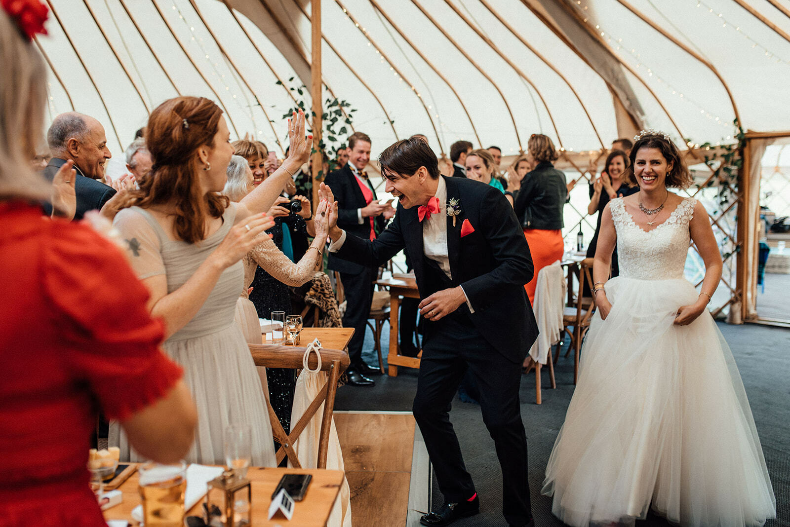 Groom high fives guests as he enters the yurt for his reception at Ilkley Golf Club