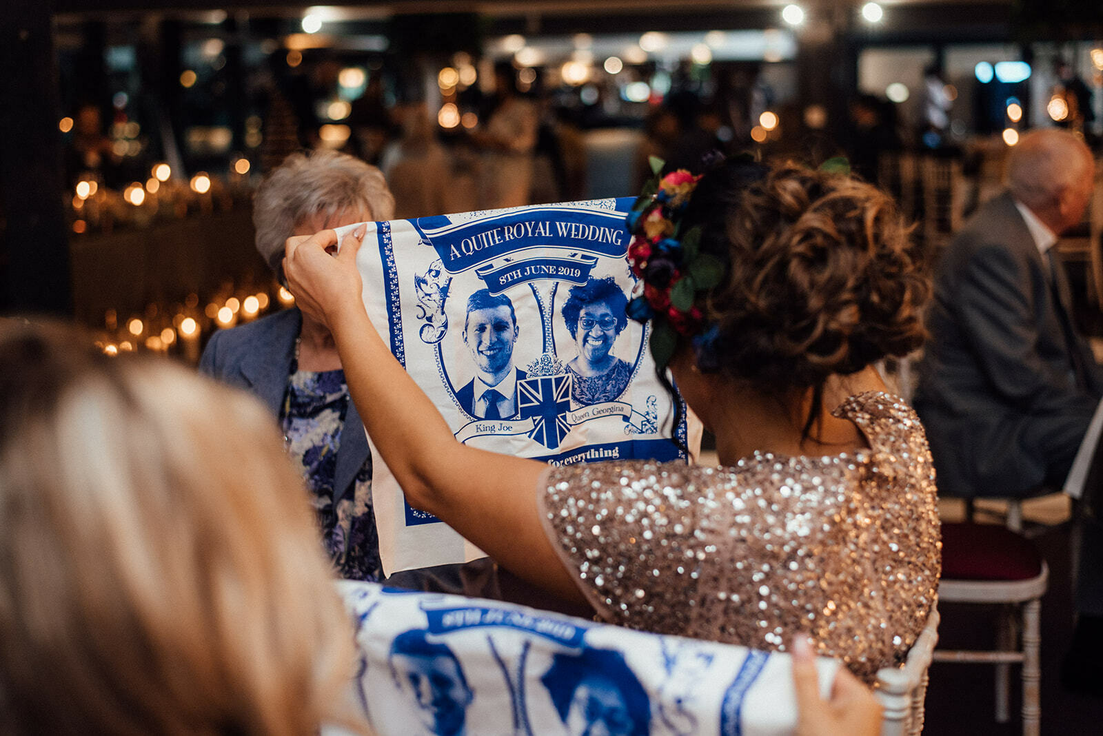 A guest holds up a novelty 'royal wedding' style tea towel