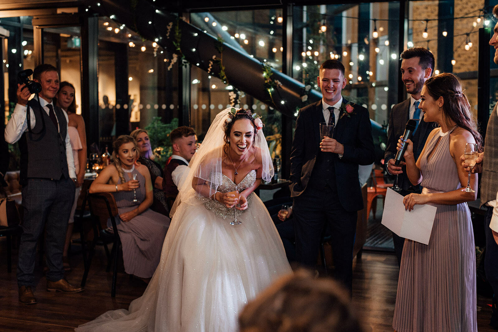 Bride laughs enthusiastically during her bridesmaids speech