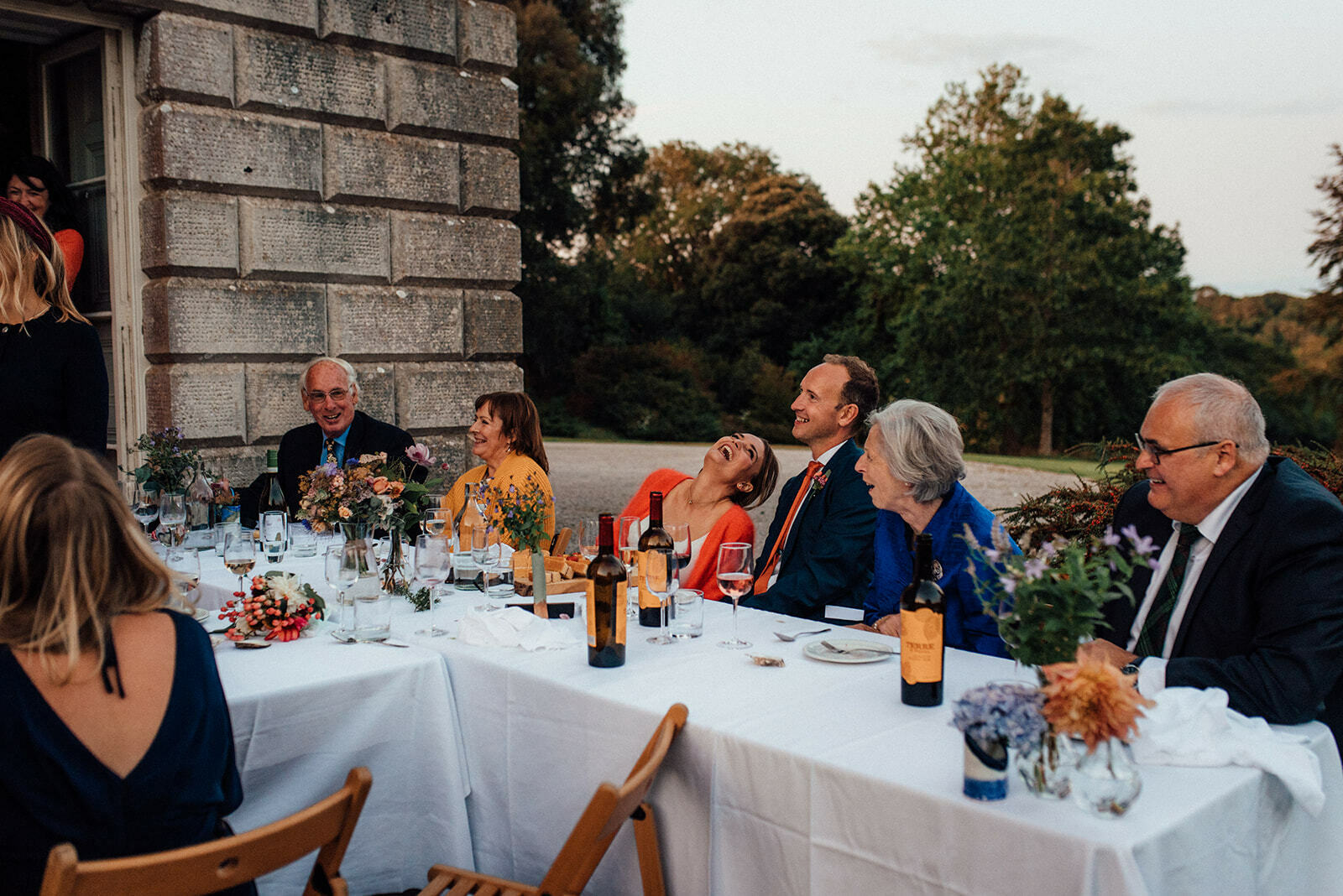 Bride and groom sat a a table with their family laughing during the speeches of their outdoor wedding