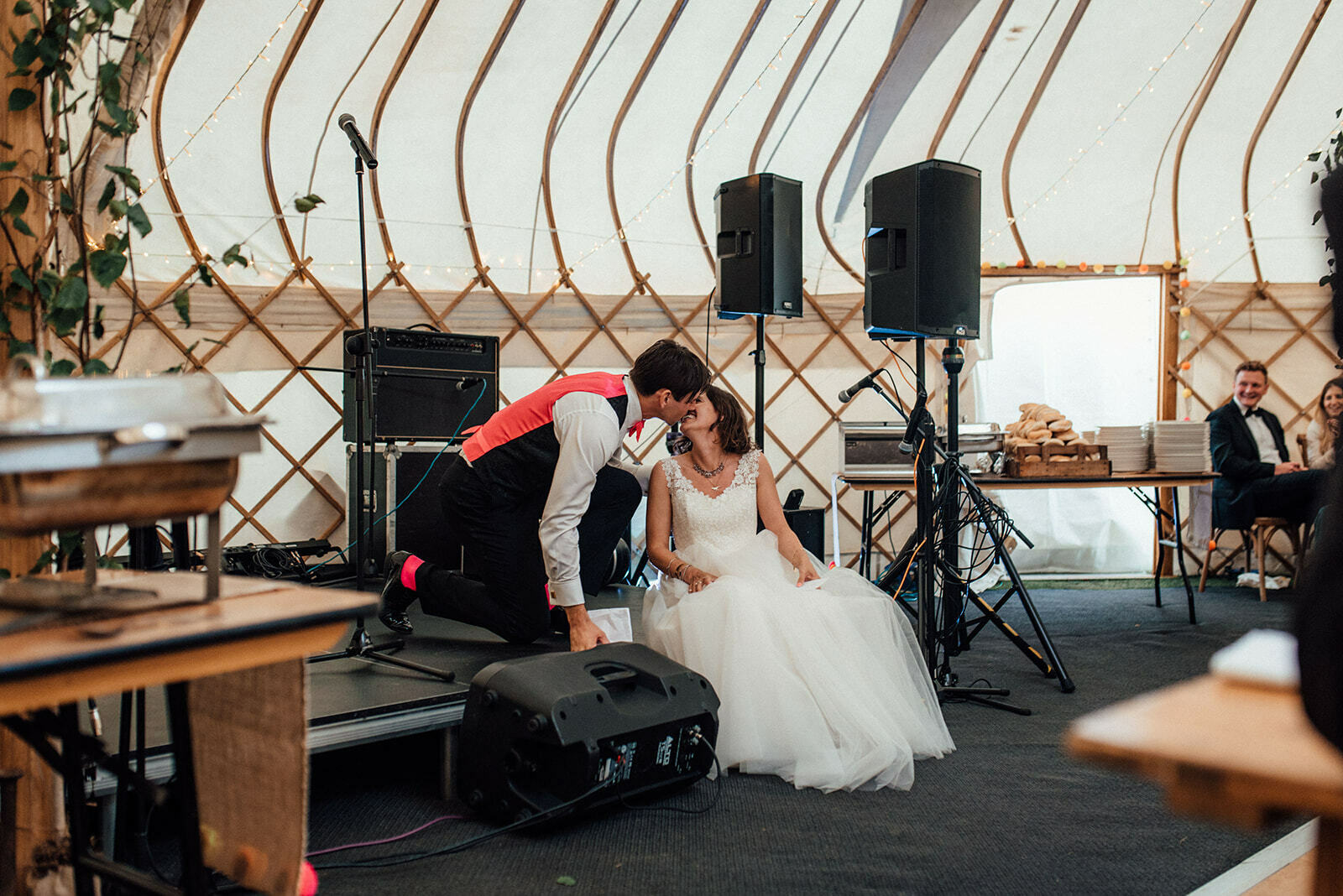 Groom kisses bride as she sits on the stage during his speech
