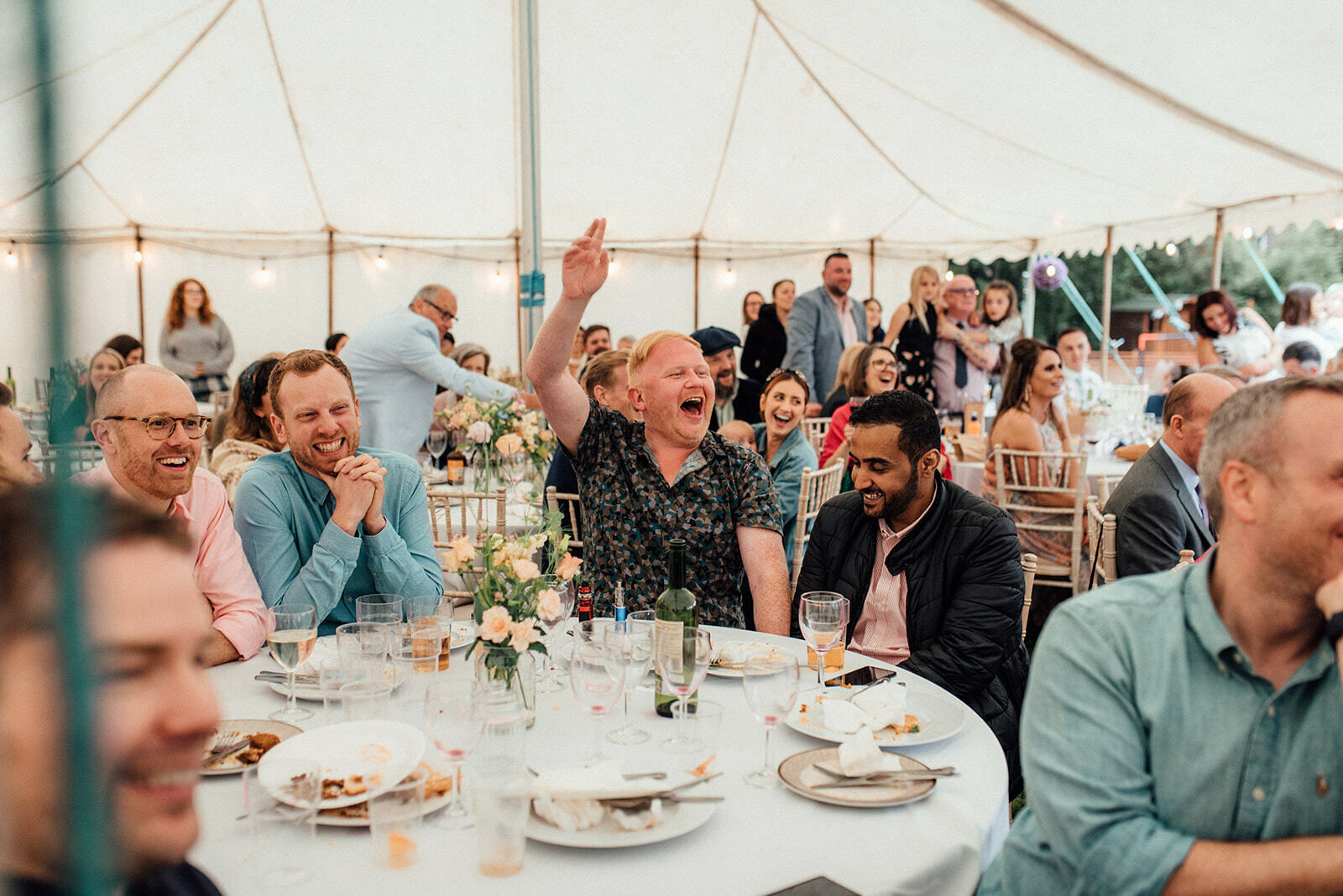 guests laugh and raise a hand as they sit round a table during a wedding at The Klondyke
