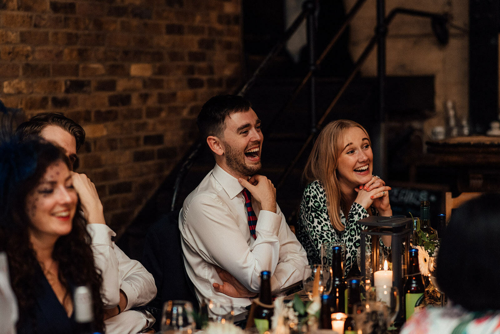 guests laugh during speeches at a wedding in The Depot N7