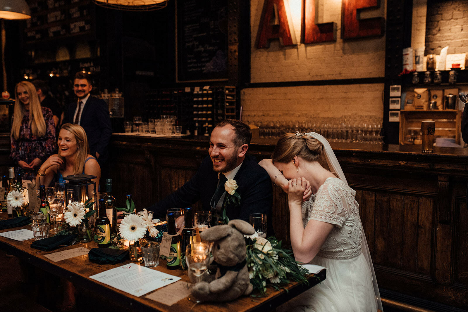 Bride hides her face on her grooms shoulder laughing at the speeches