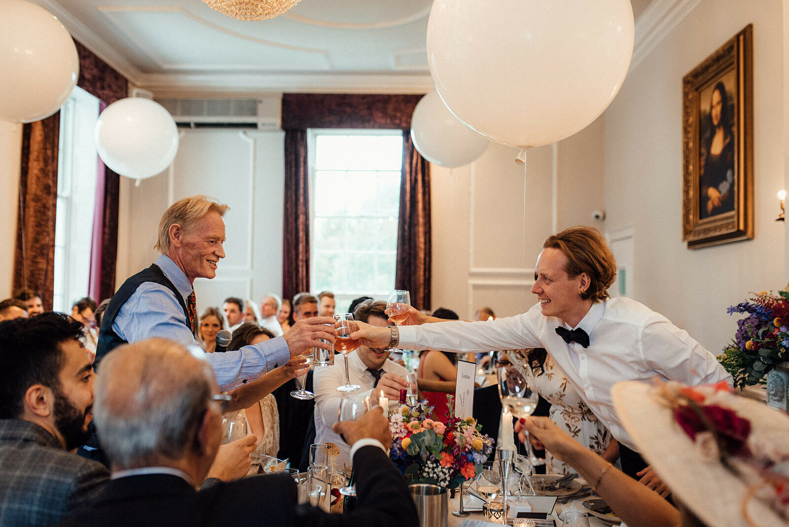Groom and his father stand and clink glasses during a wedding breakfast in Belair House