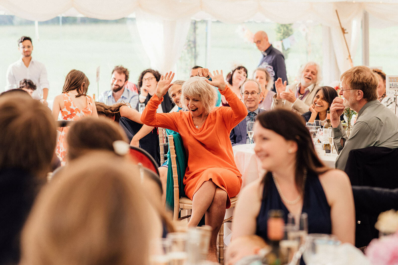 guest raises her hands in the air during speeches