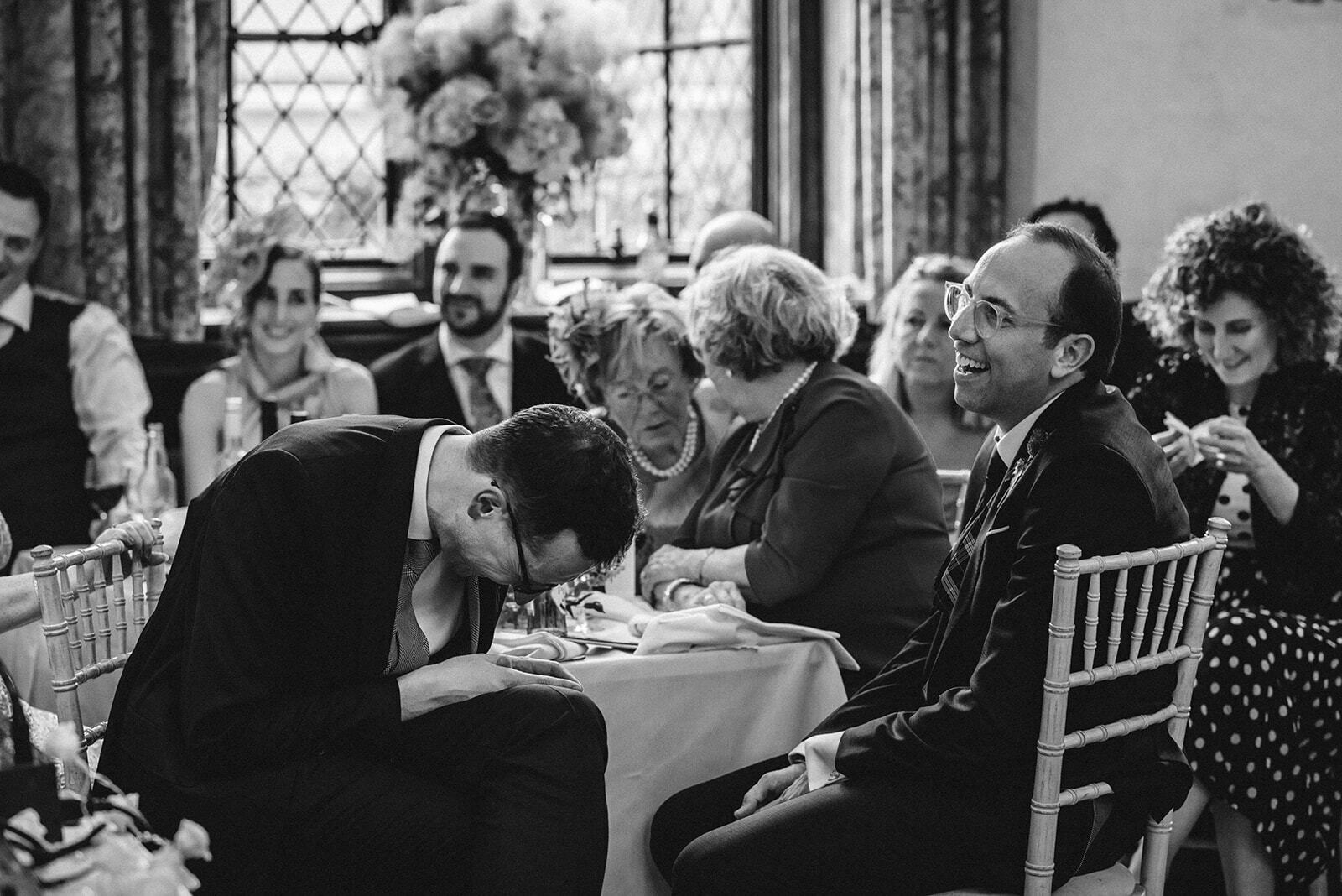 Groom's laugh together during their wedding speeches