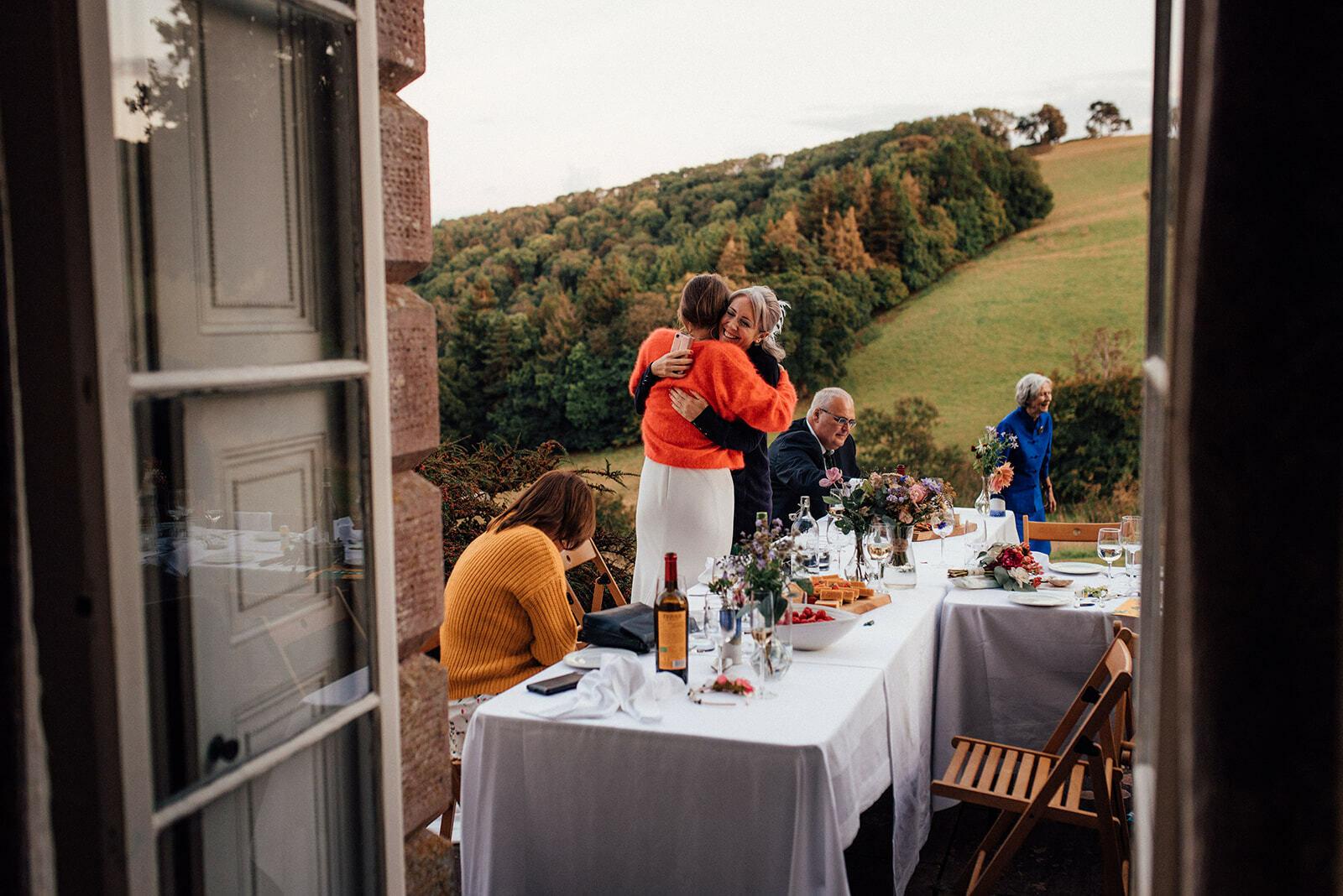 Bride hugs a guest during their alfresco wedding breakfast at Sharpham House