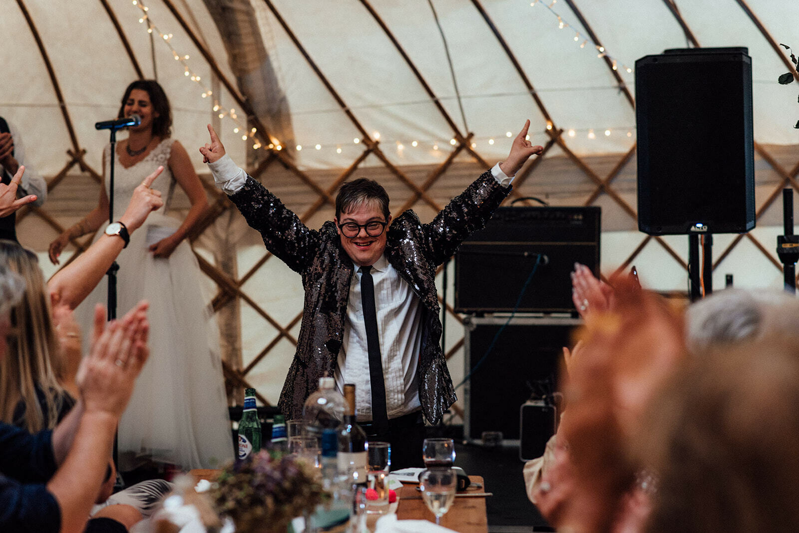 Wedding guest in a sequinned jacket raises both his hands in the air enthusiastically