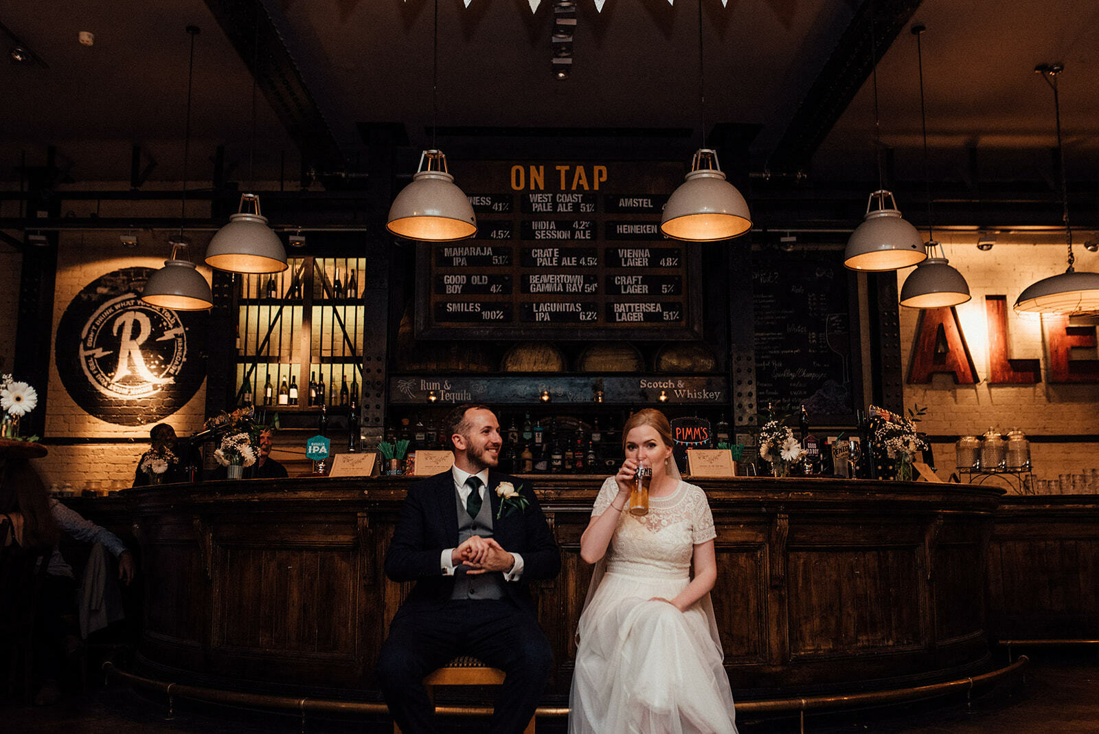 Bride and Groom sit in front of the bar at The Depot N7 during their wedding