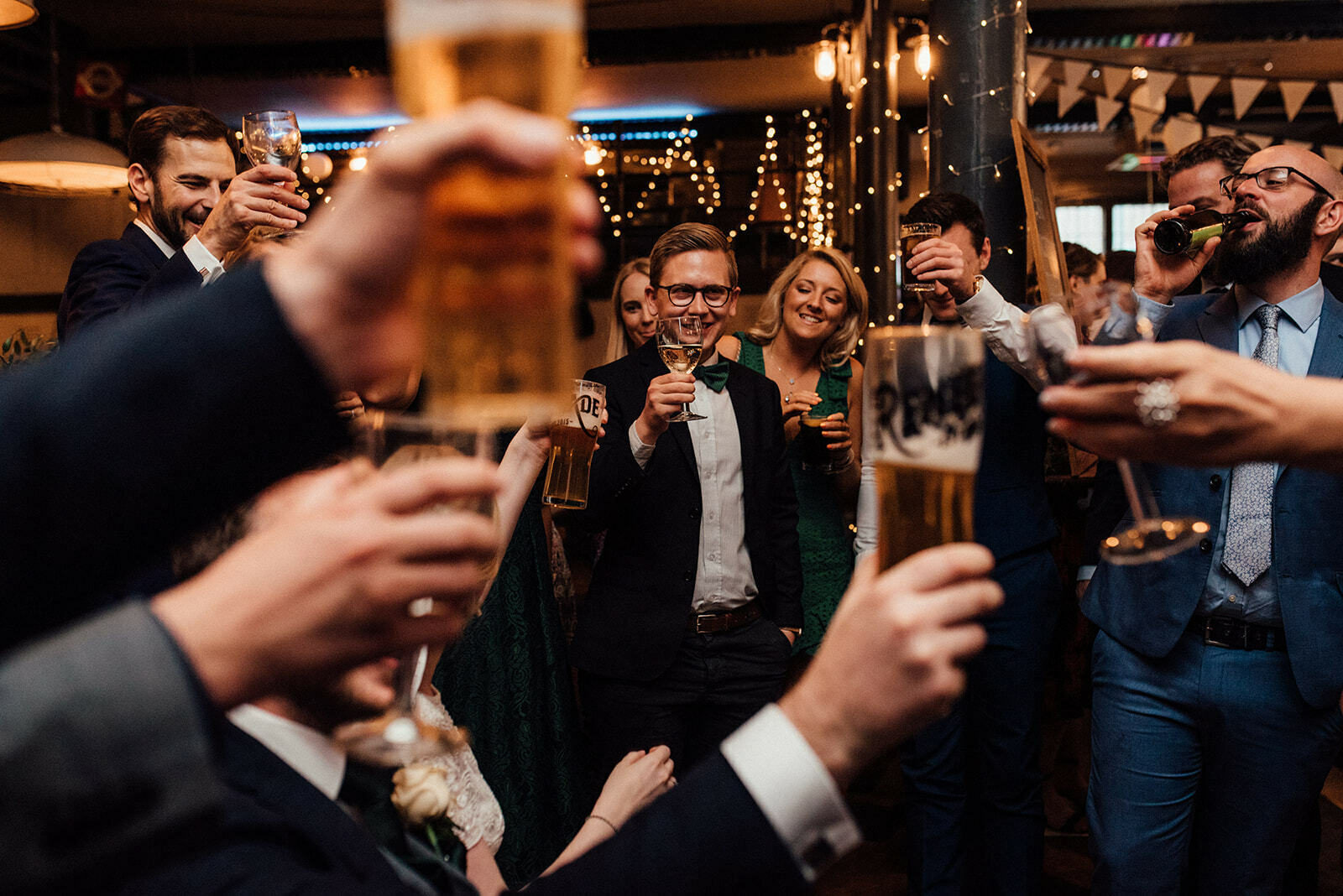 Guests all raise their glasses in celebration at a wedding in The Depot N7