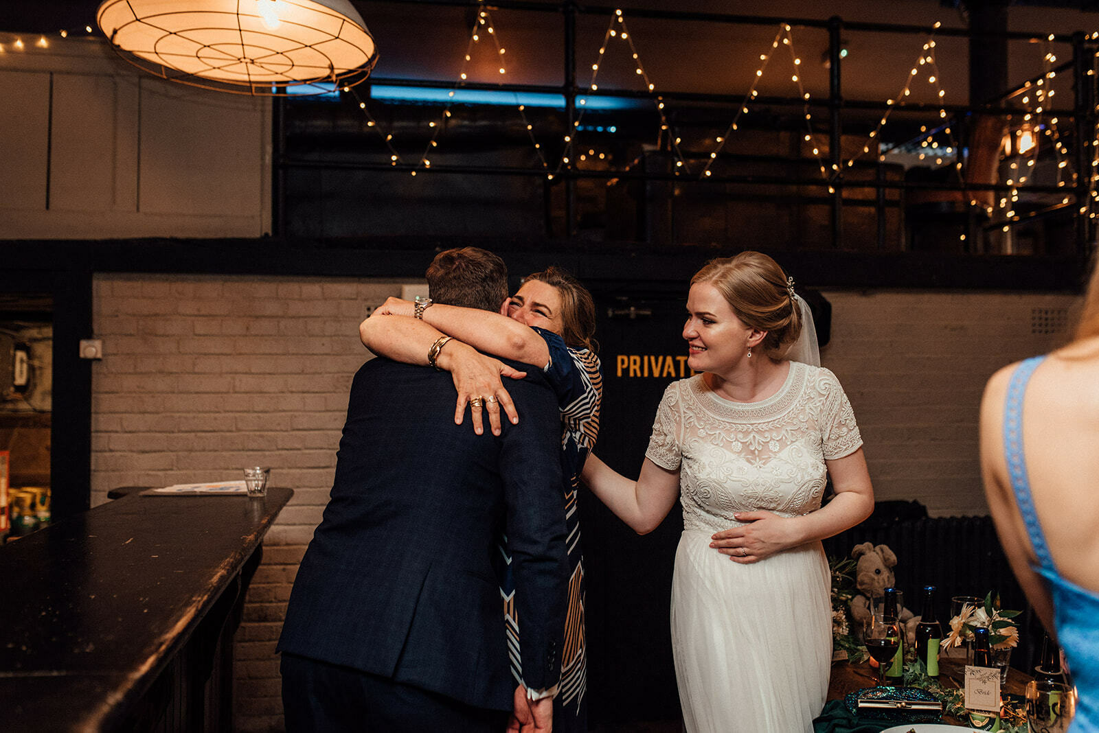 groom hugs the brides mother as the bride looks on happily